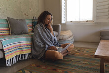 Thoughtful Caucasian Woman With Blanket Sitting On Floor Using Laptop In Sunny Cottage Living Room