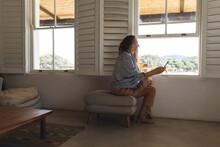 Happy Caucasian Woman Wearing Earphones Using Smartphone Sitting By Window In Cottage Living Room
