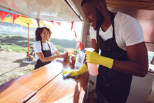Smiling Diverse Couple Behind Cleaning Counter In Food Truck
