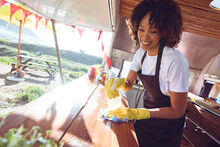 Smiling Mixed Race Woman Cleaning Counter In Food Truck