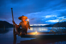 Portrait Of A Traditional Cormorant Fisherman Sitting On His Boat On Mekong River, Thailand