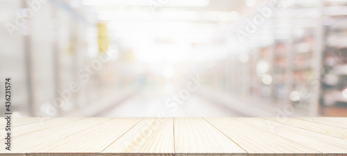 Photo Wood table top with supermarket grocery store blurred background with bokeh ligh
