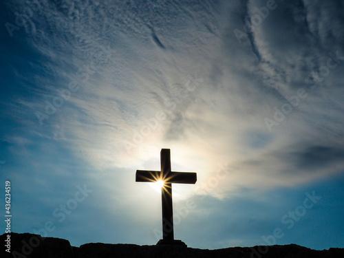 Obraz na plátně Silhouette crucifix on rock with sun ray starburst effect