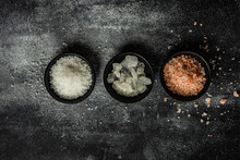 Overhead View Of Three Bowls Of Assorted Rock Salt On A Table