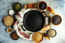 Saucepan Surrounded By Bowls Of Pumpkin Seeds, Sunflower Seeds, Flax Seeds, Chickpeas, Buckwheat, Sesame Seeds, Chilli, Oil, Peppercorns, Rice And Salt