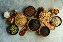 Bowls Of Pumpkin Seeds, Sunflower Seeds, Flax Seeds, Chickpeas, Sesame Seeds, Chilli, Oil, Peppercorns, Rice And Salt