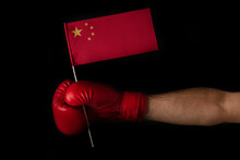 Hand In Boxing Glove Holds The Flag Of China. Black Background.