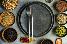 Empty Place Setting Surrounded By Bowls Of Fresh Seeds, Grains And Seasoning