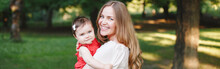 Mothers Day Holiday. Smiling Caucasian Mother And Girl Toddler Daughter Hugging In Park. Mom Embracing Child Baby On Summer Day Outdoor. Happy Authentic Family Lifestyle. Web Banner Header