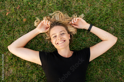 Tela Young blonde woman lying on green grass