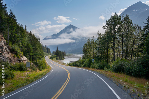 Camper travels along a curving highway in Alaska below mountains near Seward on a sunny afternoon #436245544