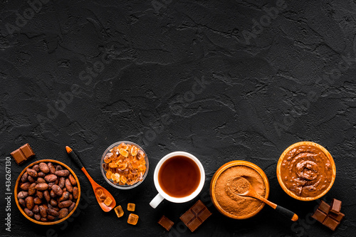 Fotografiet Coffee and cocoa beans and ground powder with hot chocolate drink