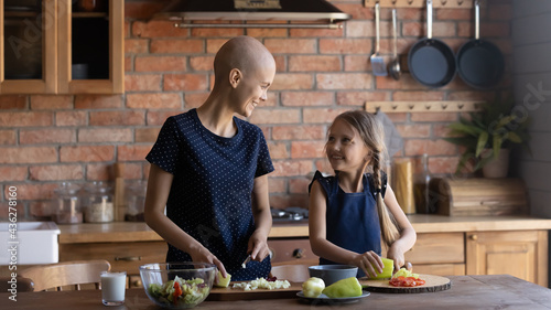 Fotografiet Happy ill mom and daughter kid talking and laughing while preparing salad and chopping fresh vegetables together