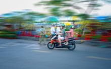 Ho Chi Minh City, Vietnam - February 9, 2021: People Vietnamese Driving A Motorbike With Holder Flower Or Kumquat Pot Behind Decoration Purposes House For Lunar New Year In Ho Chi Minh, Vietnam