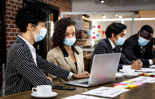 Canvas Multiracial mixed race businesspeople group working with concentration  at office, wearing face masks as new normal to protect or prevent virus in pandemic crisis, using laptop and job discussion