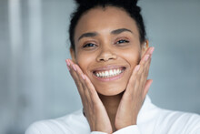 Head Shot Of Happy Joyful Black Girl Touching Face In Bathroom, Admiring Cosmetic Effect Of Moisturizing Cream, Organic Oil, Cleaning Lotion, Looking At Camera, Smiling. Skincare, Dental Care Concept