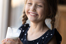 Happy Girl With Funny Moustache Drinking Milk, Holding Glass, Smiling And Laughing. Positive Child Keeping Healthy Nutrition, Getting Calcium And Vitamins From For Growth From Dairy Products