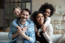 Portrait Of Happy Young Multiethnic Family With Small Diverse Daughters Relax In Living Room At Home. Smiling Multiracial Mom And Dad Cuddle Hug With Adopted Small Girls Children. Adoption Concept.