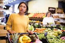Portrait Of Positive Interested Latin American Woman Visiting Supermarket Food Department For Shopping