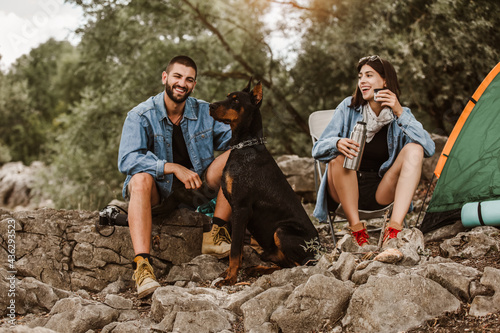 Man and woman and their doberman sitting in chairs outside the tent having coffee and talking Fototapete