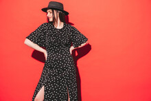 High Fashion Portrait Of Young Beautiful Woman Wearing Nice Trendy Summer Polka-dot Dress.Sexy Fashion Model Posing Near Red Wall In Studio.Fashionable Female With Red Lips And Hat. In Sunglasses