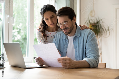 Canvastavla Happy affectionate young family couple reading paper correspondence with good news, feeling curious of getting interested information