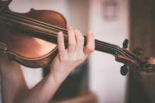 Practicing Classical Music And Violin Concept: Young Girl Happily Plays On Her New Violin