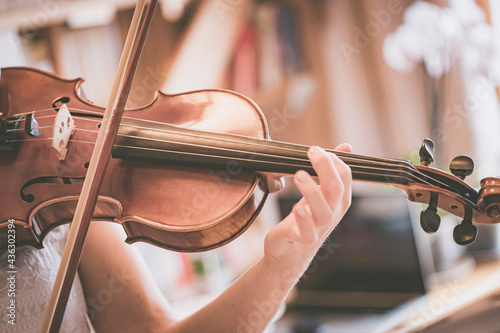 Fototapeta Practicing classical music and violin concept: Young girl happily plays on her n