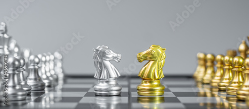 Fotografia, Obraz Gold and silver Chess Knight (horse) figure on Chessboard against opponent or enemy