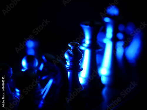 Selective focus shot of bishop chess piece illuminated with blue light against a Fototapeta