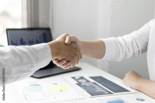 Photographie A close-up of a person shaking hands, two businessmen shaking hands after agreeing to sign a business investment contract together