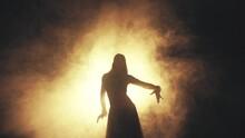 Woman Dancing In Smoke On A Dark Background