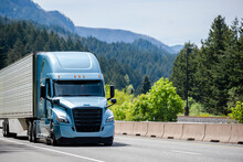 Blue Bonnet Big Rig Semi Truck With Black Grille Transporting Cargo In Refrigerator Semi Trailer Running On The Highway Road With Mountain And Forest On Background