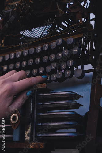 Woman's hand pressing buttons on the typewriter