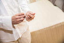 Closeup Shot Of A Man Buttoning His Shirt Cuffs