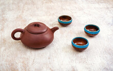 Brown Clay Teapot And Cups On Light Wooden Background
