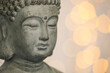 Buddha statue against blurred lights, closeup. Space for text