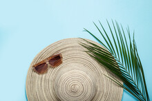 Women's Hat With Wide Brim, Sunglasses And A Branch Of A Palm Tree On A Blue Background. Summer Concept, Vacation At Sea. Banner. Flat Lay, Top View