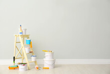 Decorator's Kit Of Tools And Paints Near Light Wall Indoors. Space For Text