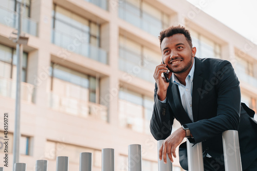 Fényképezés African-American boy in his 30s in a suit talking on a smart phone with a client of his company in a place where company buildings are seen