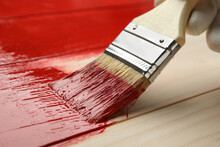 Person Painting Wooden Surface With Red Dye, Closeup