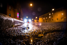 Rainy Autumn Night In The City, The Glowing Lights Of Approaching Car. Wide Angle View Of The Level Of The Curb On The Road