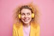 Leinwandbild Motiv Portrait of happy smiling curly woman enjoys favorite playlist listens music via wireless headphones looks away grins at camera has good mood wears yellow jacket isolated over pink background