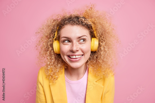 Portrait of happy smiling curly woman enjoys favorite playlist listens music via Fototapet