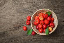 Flat Lay Of Acerola Cherry In Basket With Wooden Background.