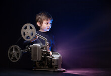 Little Boy Watching A Movie On An Old Retro Projector