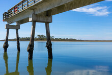Narrow Concrete Fishing Pier With Oyster And Barnacle Covered Pilings, Blue Sky Reflected In Still Waters, Tybee Island Georgia USA, Horizontal Aspect