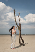 Woman In Silver Dress On Beach Holding Hand Mirror On Windy Day