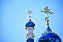 Against The Background Of A Clear Blue Sky, Two Domes Of A Christian Church Of Different Sizes, With Crosses At The Top