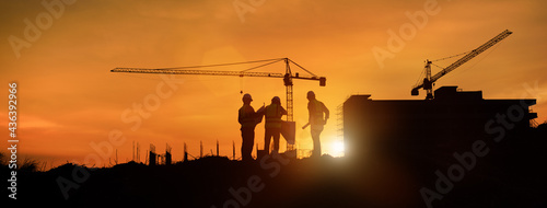 Canvas Silhouette engineer construction work control and tower crane background on natural sunset sky